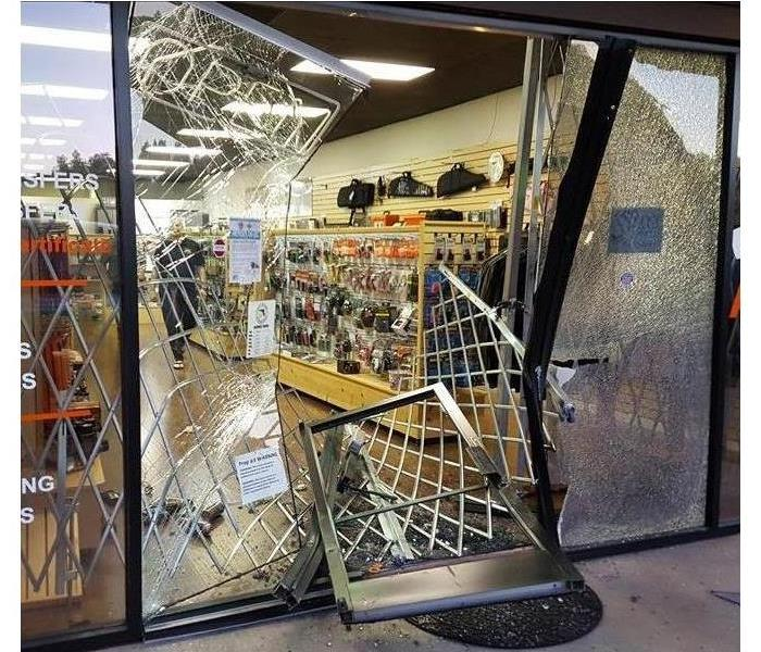 Business store front door and glass walls broken and glass all over the ground