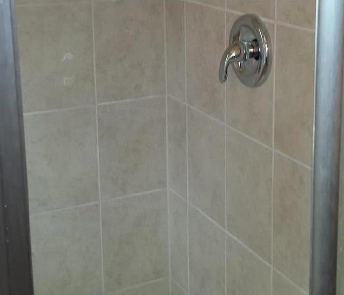 Same shower stall showing new tile installed and new faucet