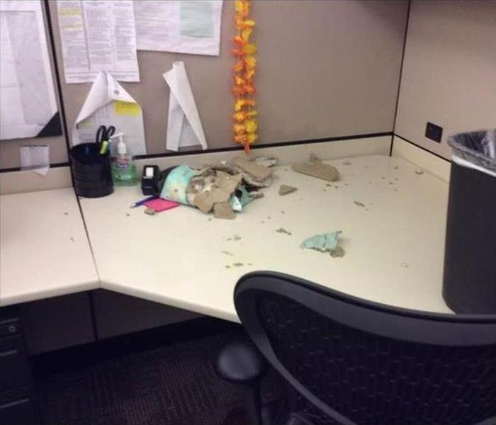 Office desk with ceiling debris fallen onto it