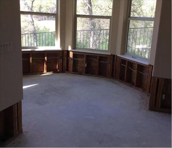 Same room showing no flooring and drywall removed