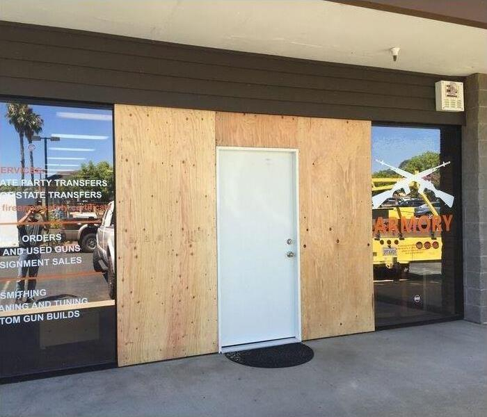 Same business front door covered by wood and new secure door installed