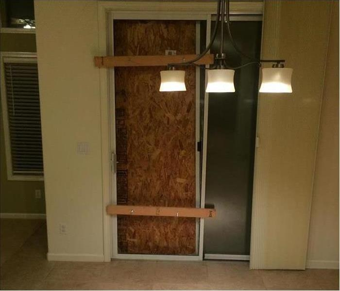 Same sliding glass door with wood covering the opening and floor cleaned