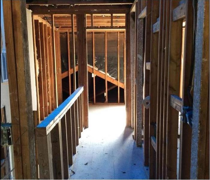 Inside of a home showing all drywall removed and only studs remaining