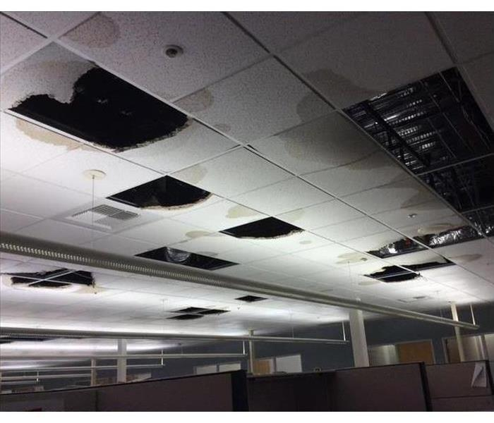 Business building showing the ceiling with tiles missing after falling down due to water damage